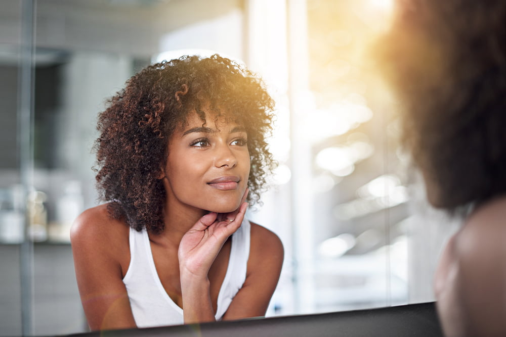 30-something woman with beautiful, healthy skin looks in the mirror