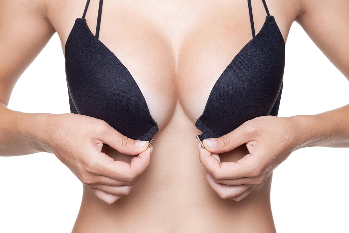 Woman unbuttons black bra after breast augmentation surgery