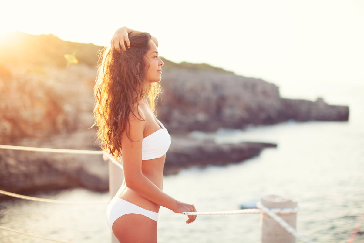 Young woman in white bikini by beach after 360 lipo and Renuvion combo treatment